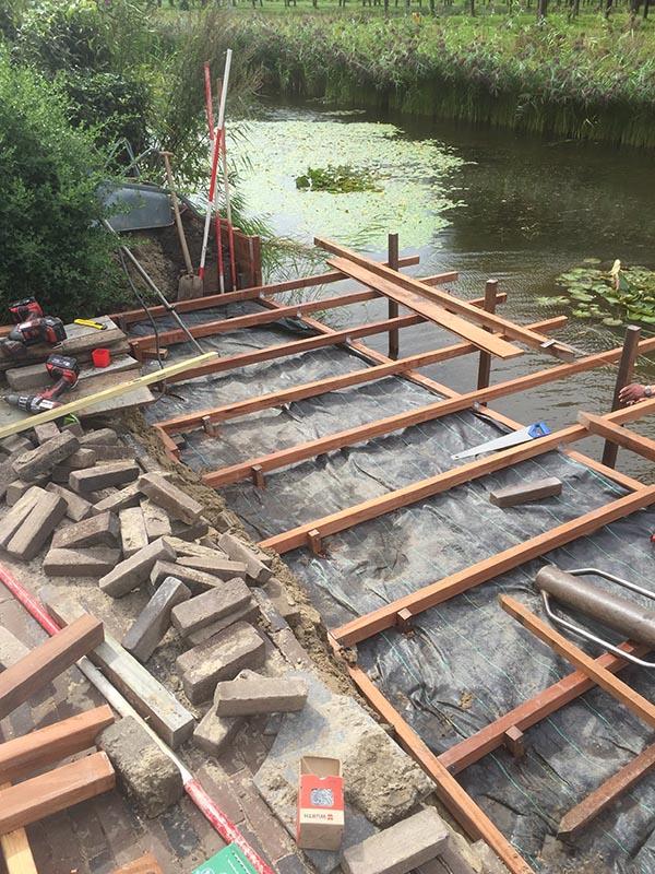 Hardhouten damwand met een overhangend terras van keramische tegels